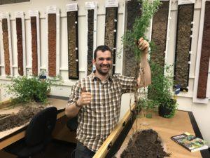 Joseph Amsili holding an alfalfa plant